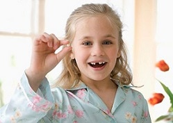 Menina segurando dente de leite
