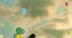 Mulher de pé em cadeira que voa suspensa por balões