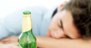 Homem dormindo segurando garrafa de cerveja