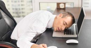 Homem dormindo com a cabeça em cima do notebook