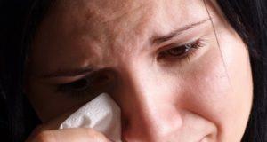 Mulher enxugando lágrimas com lenço