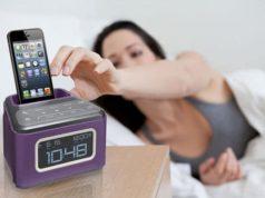 Mulher acordando e pegando smartphone