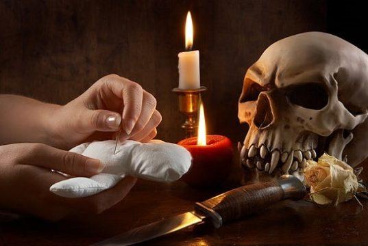 Crânio, punhal , velas e mão espetando boneco de pano