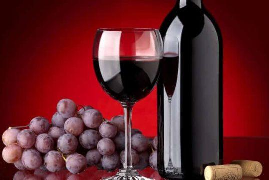 Garrafa de vinho, taça com vinho e uvas