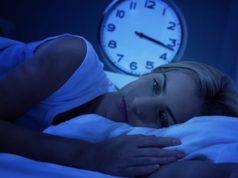 Mulher com insônia deitada na cama