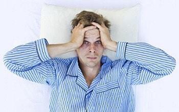 Homem com olheiras deitado na cama acordado