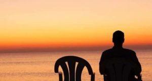 Silhueta de pessoa sentada ao lado de uma cadeira vazia