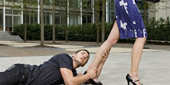 Homem deitado no chão agarrando tornozelo de mulher que caminha