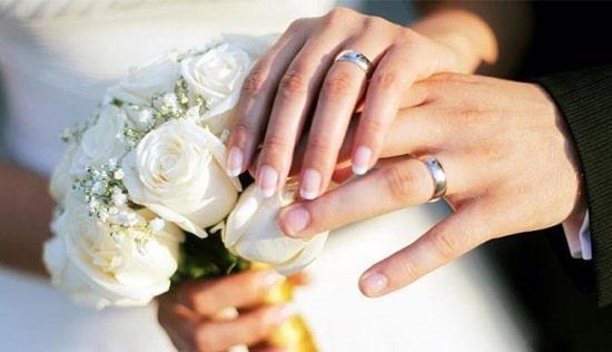 Mãos de noivos sobre buquê